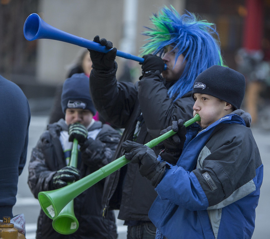 . Seattle Seahawks fans Nicholas Anderson, 12, Jonathan Anderson, 14 and Jason Anderson, 12 (twin with Nicolas) toot their hawks horns trying to stay warm as they wait for the Super Bowl champions parade to begin Wednesday, Feb. 5, 2014, in Seattle.  (AP Photo/The Seattle Times, Steve Ringman)