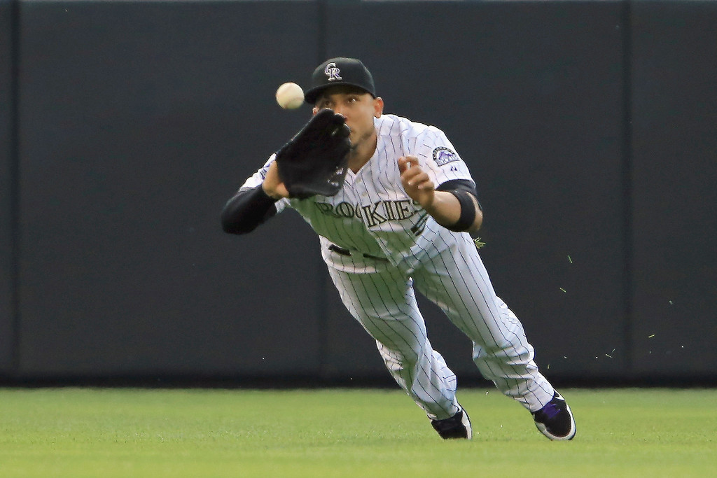 . Leftfielder Carlos Gonzalez #5 of the Colorado Rockies dives to catcha line drive by Jeff Kobernus #26 of the Washington Nationals to end the third inning at Coors Field on June 12, 2013 in Denver, Colorado.  (Photo by Doug Pensinger/Getty Images)