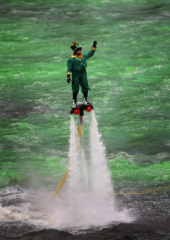 . A man dressed as a leprechaun entertains the crowd on a water propelled Flyboard while workers dye the Chicago River green to kick off the city\'s St. Patrick\'s day celebration on March 16, 2013 in Chicago, Illinois. The dying of the river has been a tradition in the city for 43 years.  (Photo by Scott Olson/Getty Images)