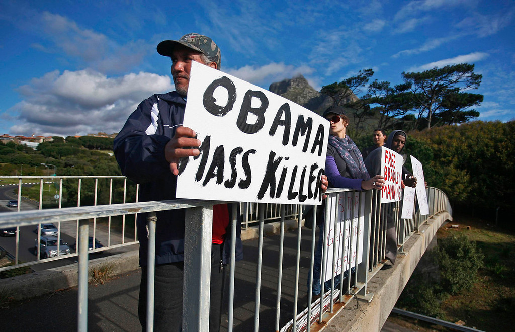 . Protesters hold placards on a bridge near the University of Cape Town ahead of a visit by U.S. President Barack Obama in Cape Town, South Africa on June 30, 2013.  REUTERS/Mark Wessels