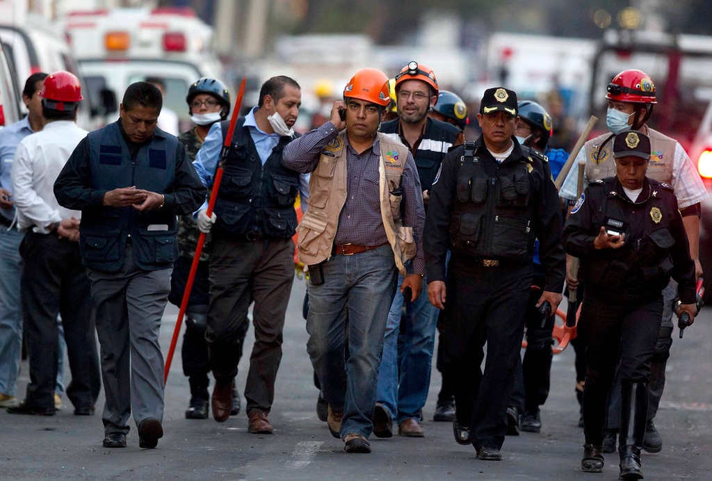 . Emergency responders walk toward the site on an explosion at a building part of Mexico\'s state-owned oil company PEMEX complex, in Mexico City, Thursday Jan. 31, 2013. The explosion killed at least 14 people . (AP Photo/Eduardo Verdugo)