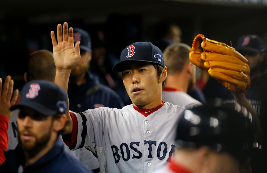 . Boston Red Sox\'s Koji Uehara is greeted in the dugout after pitching in the eighth inning during Game 5 of the American League baseball championship series against the Detroit Tigers, Thursday, Oct. 17, 2013, in Detroit. (AP Photo/Paul Sancya)
