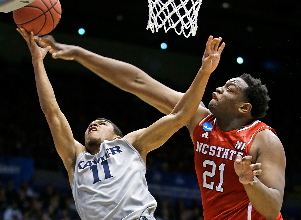 . Xavier guard Dee Davis (11) shoots against North Carolina State forward Beejay Anya (21) during the first half of a first-round game of the NCAA college basketball tournament, Tuesday, March 18, 2014, in Dayton, Ohio. (AP Photo/Al Behrman)