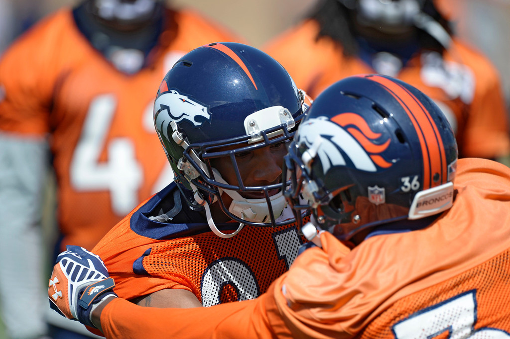 . Denver Broncos Aqib Talib (21) runs through drills with Kayvon Webster (36) during OTAs June 11, 2014 at Dove Valley. (Photo by John Leyba/The Denver Post)