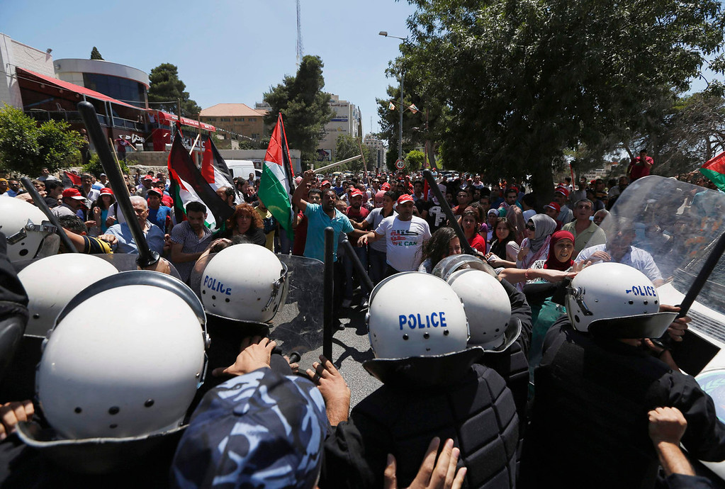 . Palestinian police officers stand in front of protesters during a demonstration against the renewal of stalled peace talks with Israel, in the West Bank city of Ramallah July 28, 2013. Israel was expected on Sunday to approve releasing more than 100 Arab prisoners as a step to renew stalled peace talks with the Palestinians ahead of plans to convene negotiators in Washington later this week. REUTERS/Mohamad Torokman