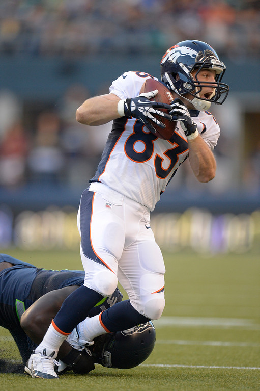 . SEATTLE, WA. - AUGUST 17: Denver Broncos wide receiver Wes Welker (83) catches a pass as he is brought down by Seattle Seahawks strong safety Kam Chancellor (31) in the first quarter August 17, 2013 at Century Link Field. (Photo By John Leyba/The Denver Post)