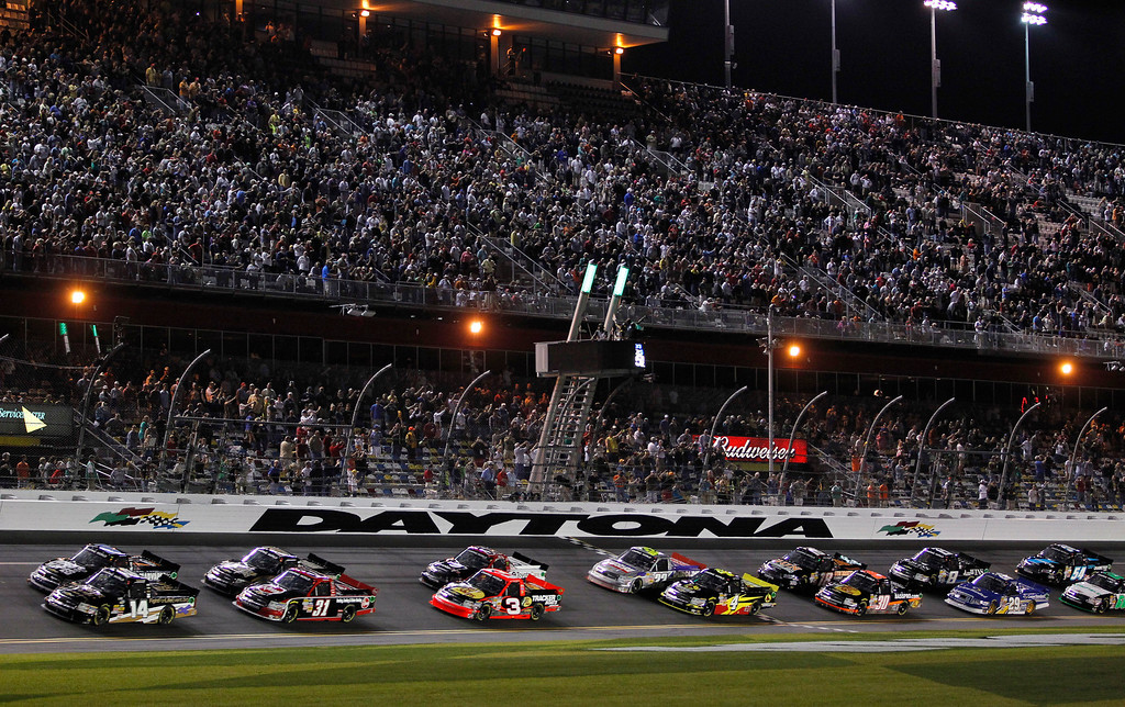. Pole-sitter Brennan Newberry (14) leads a group of trucks past the starting line to begin the the NASCAR Truck Series auto race at Daytona International Speedway, Friday, Feb. 22, 2013, in Daytona Beach, Fla. (AP Photo/Terry Renna)