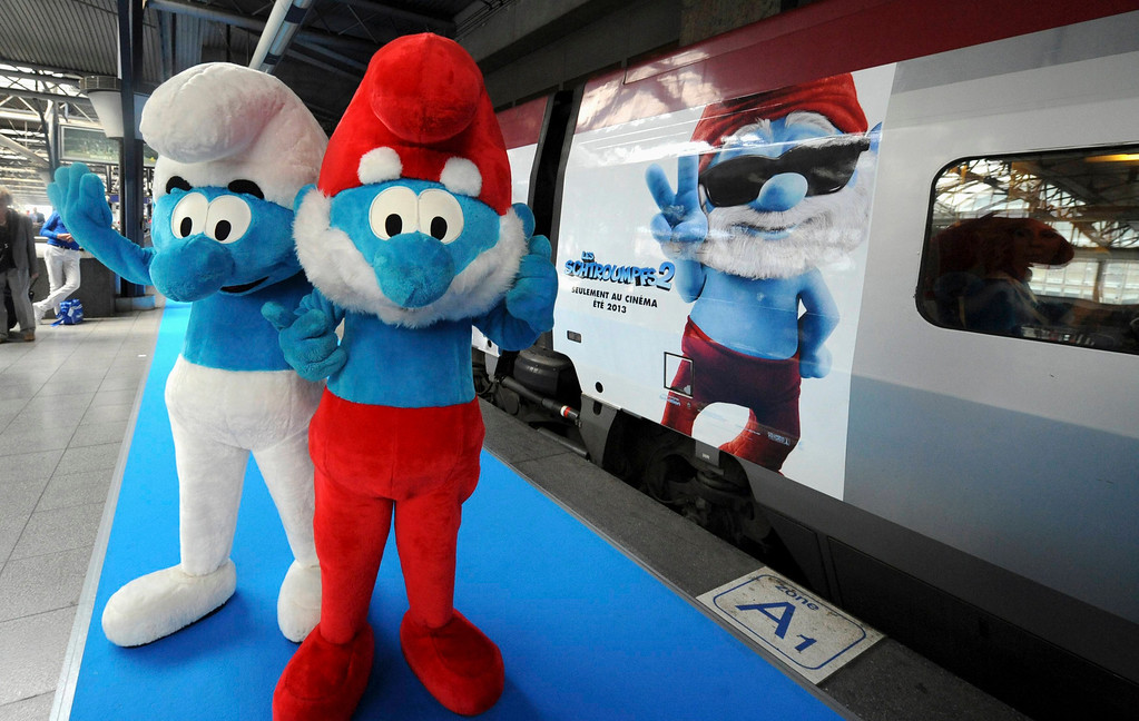 """. Life-size characters of Papa Smurf (R) and a Smurf pose next to a Thalys train decorated for the film \""""The Smurfs 2\"""" during a celebration for the birthday of Peyo, the creator of the Smurfs, on \""""Global Smurfs Day\"""" in Brussels June 22, 2013. The event was held ahead of the release of the film, according to organisers. REUTERS/Laurent Dubrule"""