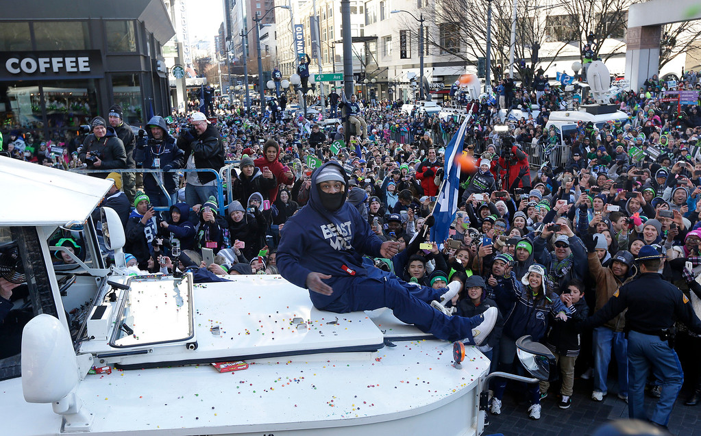 . Seattle Seahawks\' running back Marshawn Lynch throws pieces of candy while riding on the hood of a vehicle during the Super Bowl champions parade, Wednesday, Feb. 5, 2014, in Seattle. (AP Photo/Ted S. Warren)
