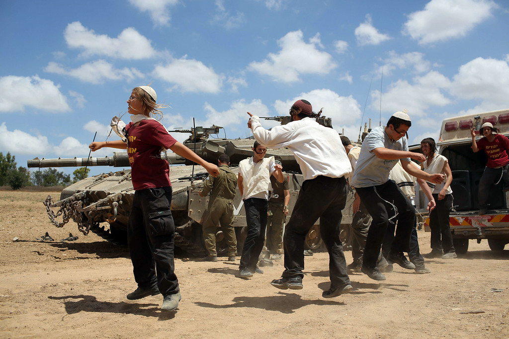 ". Young Orthodox Jews dance to support the soldiers at an army deployment area near Israel\'s border with the Gaza Strip, on July 17, 2014. An Israeli official said the Jewish state had agreed a ceasefire with Hamas that will begin at 0300 GMT Friday, but the Islamist movement said it had ""no information\"" on a deal. AFP PHOTO /MENAHEM KAHANA/AFP/Getty Images"