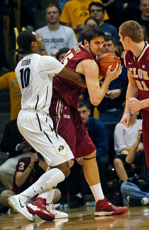. Elon\'s Tony Sabato, center, fights for control of the ball with Colorado\'s Tre\'Shaun Fletcher, left, during the first half of an NCAA college basketball game in Boulder, Colo., Friday, Dec. 13, 2013. (AP Photo/Brennan Linsley)
