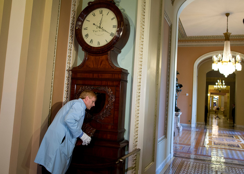 . Richard Doerner, Museum Specialist for the U.S. Senate Commission on Art, listens to the Ohio Clock as he restarts it outside the Senate chamber on Capitol Hill on Thursday, Oct. 17, 2013 in Washington. The clock stopped during the 16 day government shutdown because the workers that care for the clock were furloughed. (AP Photo/ Evan Vucci)