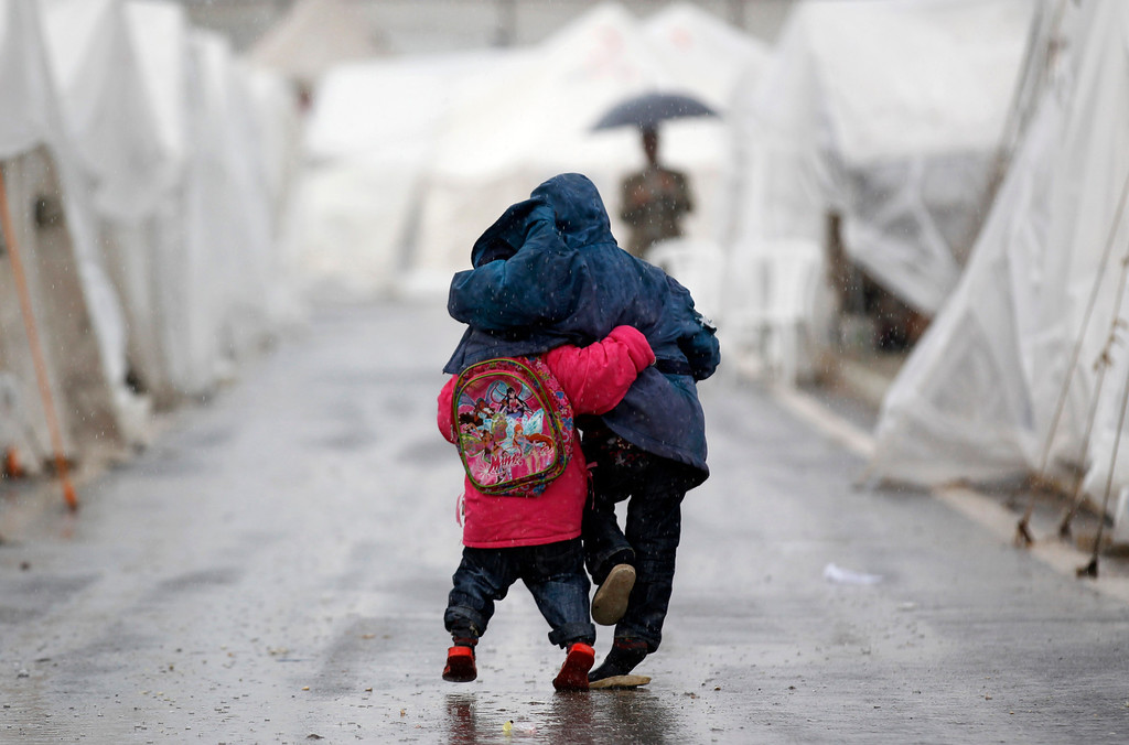 . Syrian boys walk shoulder to shoulder in the rain at the Boynuyogun refugee camp on the Turkish-Syrian border in Hatay province February 8, 2012. There are 1,750 Syrian refugees living in the camp which was set up by the Turkish Red Crescent. The Turkish Foreign Ministry says there are currently some 10,000 Syrian refugees living in six different camps in Turkey.  REUTERS/Murad Sezer