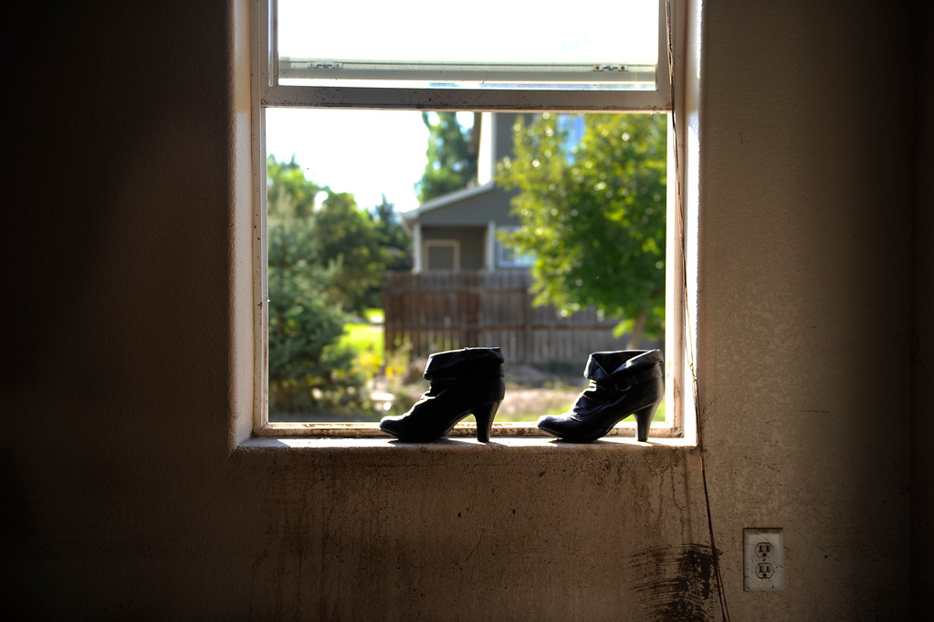 . The dress boots that Fatima Payan shared with her daughter Fernanda dried in the window of their flooded home in Evans Saturday. The family did not have insurance. Residents of Evans continued the grim work of salvaging personal belongings from flooded homes Saturday afternoon, September 21, 2013.  Photo By Karl Gehring/The Denver Post