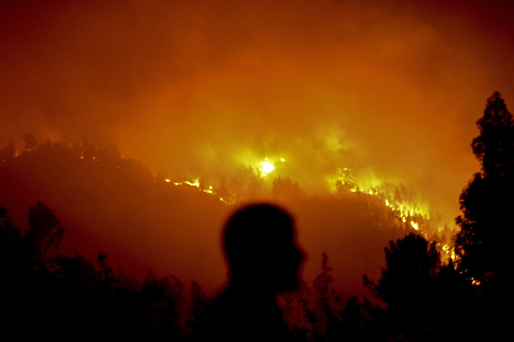 . A man stands watching a wildfire in Santiago de Besteiros, near Caramulo, central Portugal, early on August 30, 2013.   AFP PHOTO / PATRICIA DE MELO MOREIRA/AFP/Getty Images