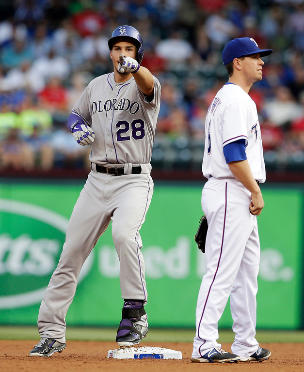 . Texas Rangers\' Donnie Murphy stands by the bag as Colorado Rockies\' Nolan Arenado (28) points to the dugout after hitting a two-run double off a pitch from Rangers starter Colby Lewis in the first inning of a baseball game, Wednesday, May 7, 2014, in Arlington, Texas. The hit that gives Arenado a 27-game hitting streak scored Carlos Gonzalez and Troy Tulowitzki. (AP Photo/Tony Gutierrez)