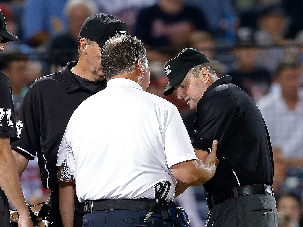 . Home plate umpire Marty Foster, right, is checked by Atlanta Braves trainer Jim Lovell after being hit in the arm by a pitch during a baseball game between the Colorado Rockies and the Atlanta Braves in Atlanta, Wednesday, July 31, 2013. Foster left the game. (AP Photo/John Bazemore)