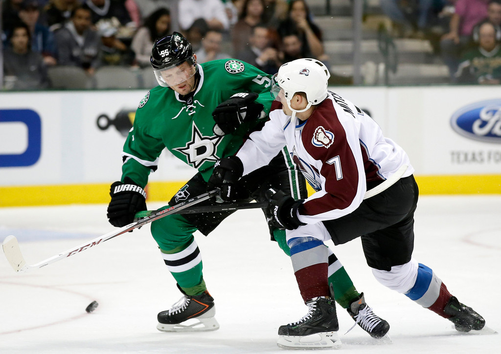 . Dallas Stars\' Sergei Gonchar (55), of Russia, and Colorado Avalanche\'s John Mitchell (7) avoid a collision while competing for a loose puck in the first period of an NHL hockey game, Friday, Nov. 1, 2013, in Dallas. (AP Photo/Tony Gutierrez)