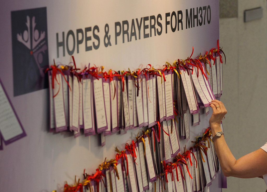 . A woman read message cards tied up for passengers aboard a missing Malaysia Airlines plane, at a shopping mall in Kuala Lumpur, Malaysia, Monday, March 24, 2014. A Chinese plane on Monday spotted two white, square-shaped objects in an area identified by satellite imagery as containing possible debris from the missing Malaysian airliner, while the United States separately prepared to send a specialized device that can locate black boxes. (AP Photo)