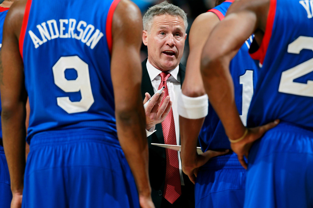 . Philadelphia 76ers head coach Brett Brown, center, confers with players during a timeout against the Denver Nuggets in the fourth quarter of the Sixers\' 114-102 victory in an NBA basketball game in Denver on Wednesday, Jan. 1, 2014. (AP Photo/David Zalubowski)