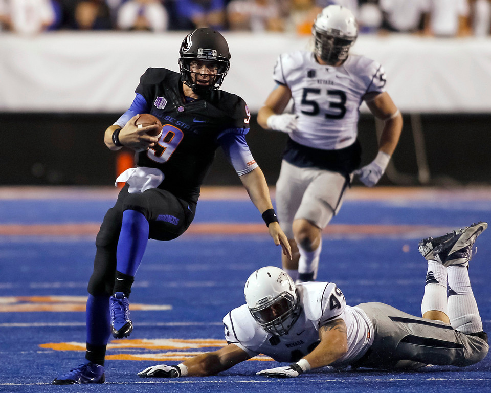 . Boise State quarterback Grant Hedrick (9) runs the ball past Nevada linebacker Jordan Dobrich (49) during the first half of an NCAA college football game in Boise, Idaho, Saturday, Oct. 19, 2013. (AP Photo/Otto Kitsinger)
