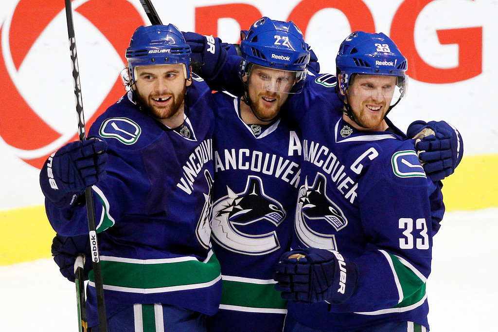 . Vancouver Canucks\' (L-R) Zack Kassian, Daniel Sedin and Henrik Sedin celebrate Kassian\'s goal against the Colorado Avalanche during the third period of their NHL hockey game in Vancouver, British Columbia January 30, 2013.   REUTERS/Ben Nelms
