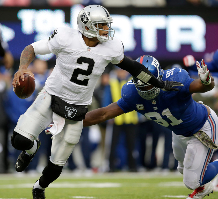 . Oakland Raiders quarterback Terrelle Pryor (2) tries to avoid being hit by New York Giants defensive end Justin Tuck (91) during the second half of an NFL football game, Sunday, Nov. 10, 2013, in East Rutherford, N.J. (AP Photo/Kathy Willens)