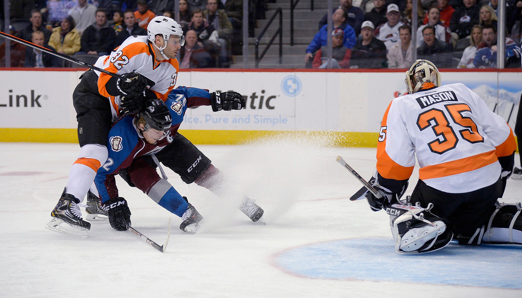 . Colorado Avalanche left wing Gabriel Landeskog (92) ducks down as Philadelphia Flyers defenseman Mark Streit (32) gets hit and flips over him during the first period January 2, 2014 at Pepsi Center. (Photo by John Leyba/The Denver Post)