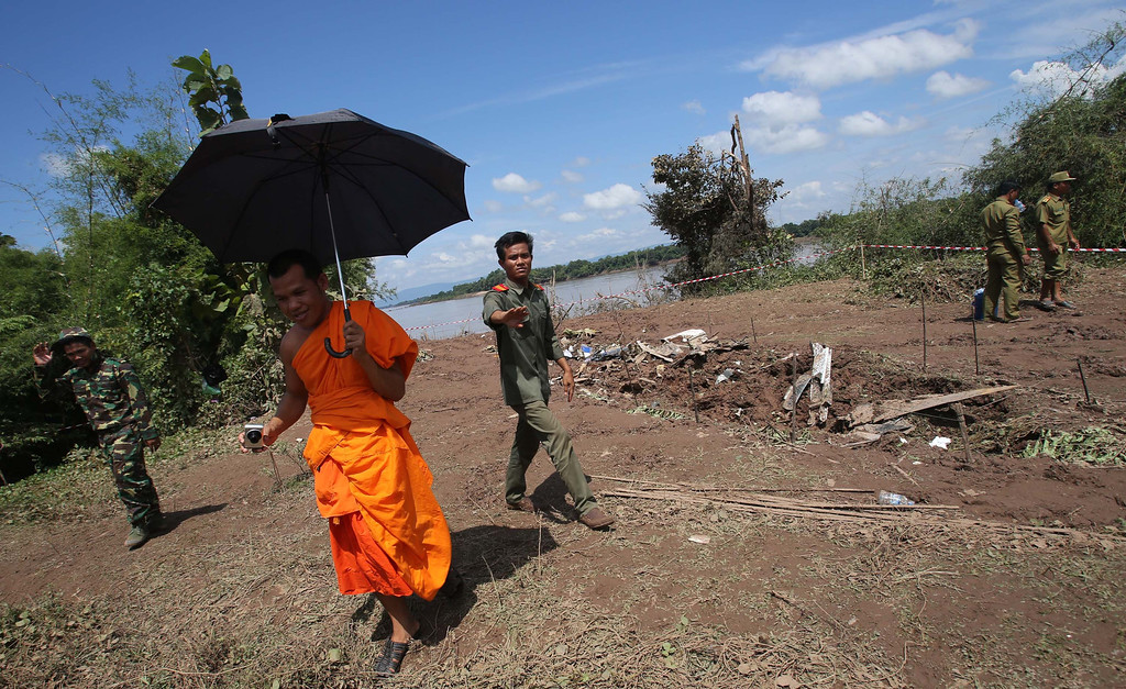 . Lao soldiers ask a monk to leave from the crash site of a Laos Airlines plane in Pakse, Laos Thursday, Oct. 17, 2013.  (AP photo/Sakchai lalit)