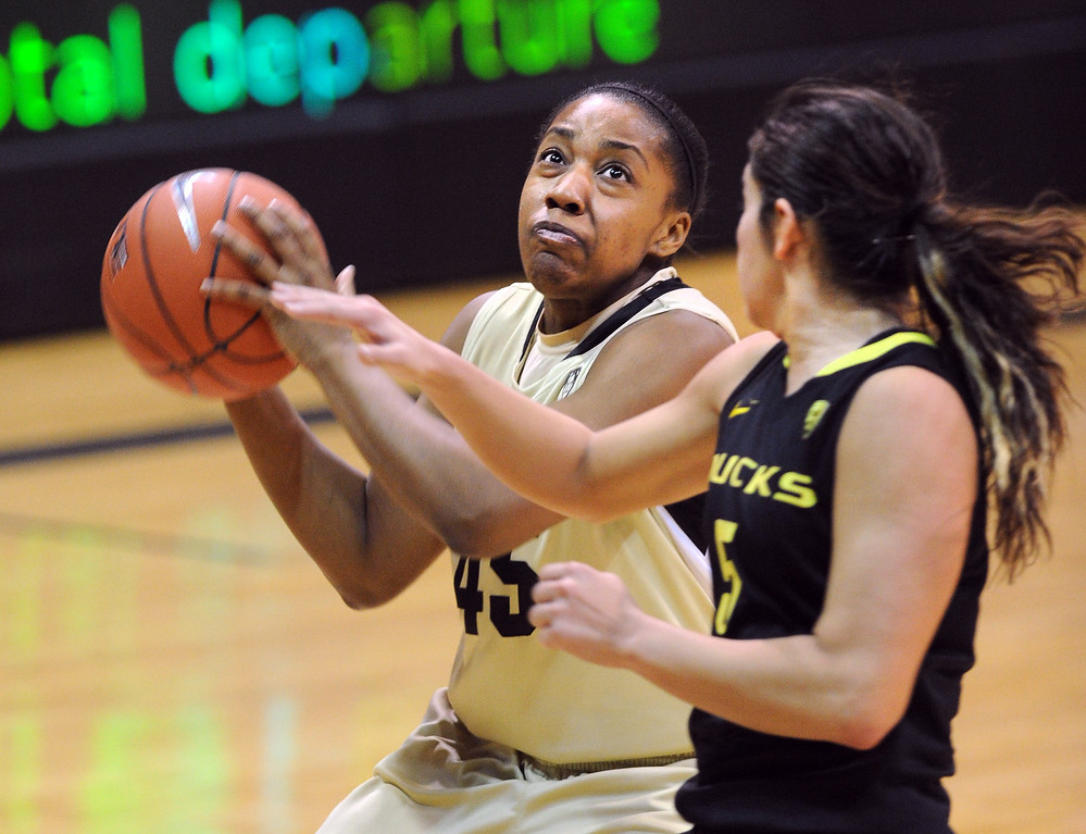 . Kyleesha Weston of CU goes to the basket on Jordan Loera of Oregon. Cliff Grassmick / February 10, 2013