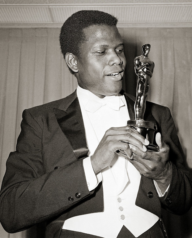 """. Actor Sidney Poitier is photographed with his Oscar statuette at the 36th Annual Academy Awards in Santa Monica, Calif. on April 13, 1964. He won Best Actor for his role in \""""Lillies of the Field.\""""   Poitier became the first black person to win an Academy Award for Best Actor. (AP Photo)"""