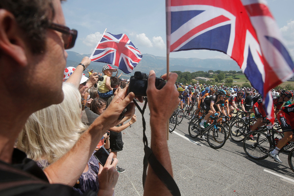 . The pack passes spectators waving British flags during the fifteenth stage of the Tour de France cycling race over 242.5 kilometers (150.7 miles) with start in in Givors and finish on the summit of Mont Ventoux pass, France, Sunday July 14, 2013. The riders climbed to an altitude of 1912 meters (6,273 Feet) tackling Mont Ventoux pass at the end of the longest stage of the 100th Tour de France edition. (AP Photo/Laurent Cipriani)