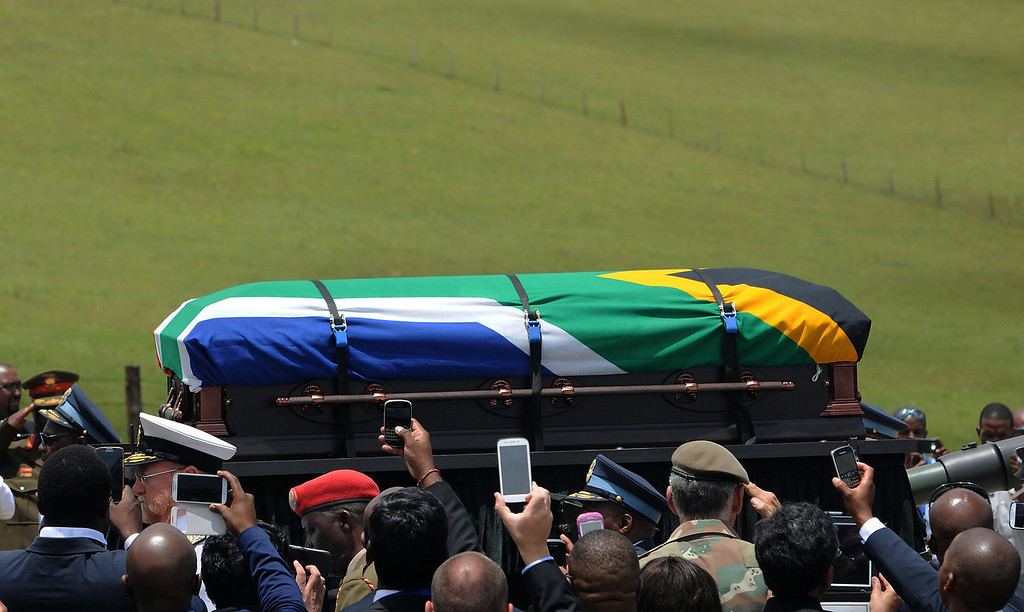 . Guests attending the funeral service for former South African President Nelson Mandela take cell phone photos as Mandela\'s casket is taken to its burial place in Qunu, South Africa, Sunday, Dec. 15, 2013. (AP Photo/Felix Dlangamandla, Pool)