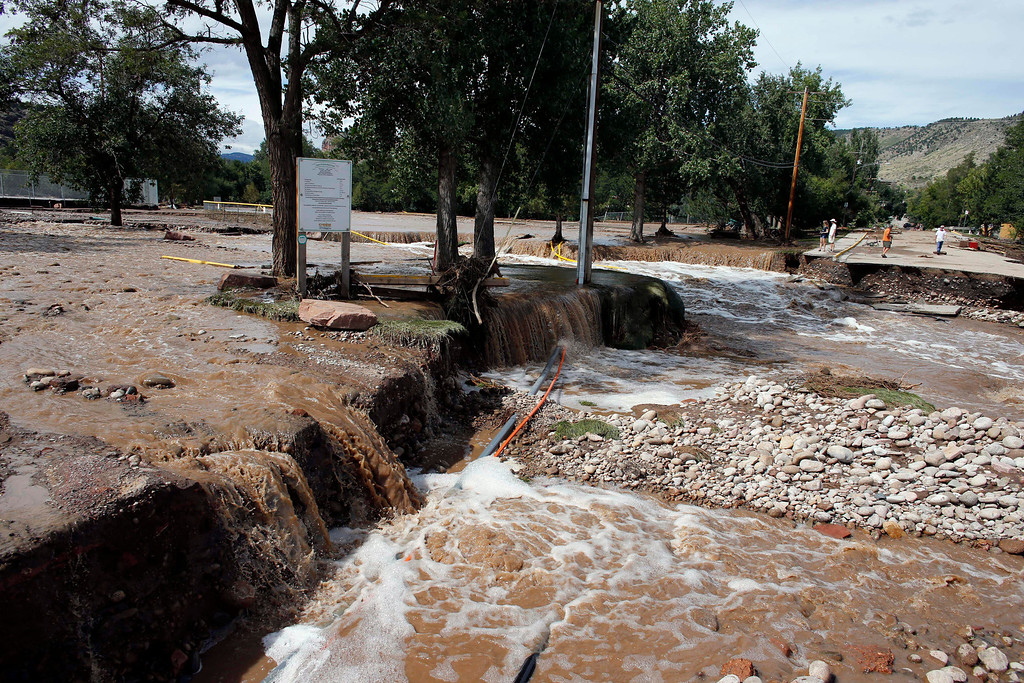 . Water rushes past where a bridge collapsed in a flash flood, in Lyons, Colo., Friday Sept. 13, 2013.  (AP Photo/Brennan Linsley)