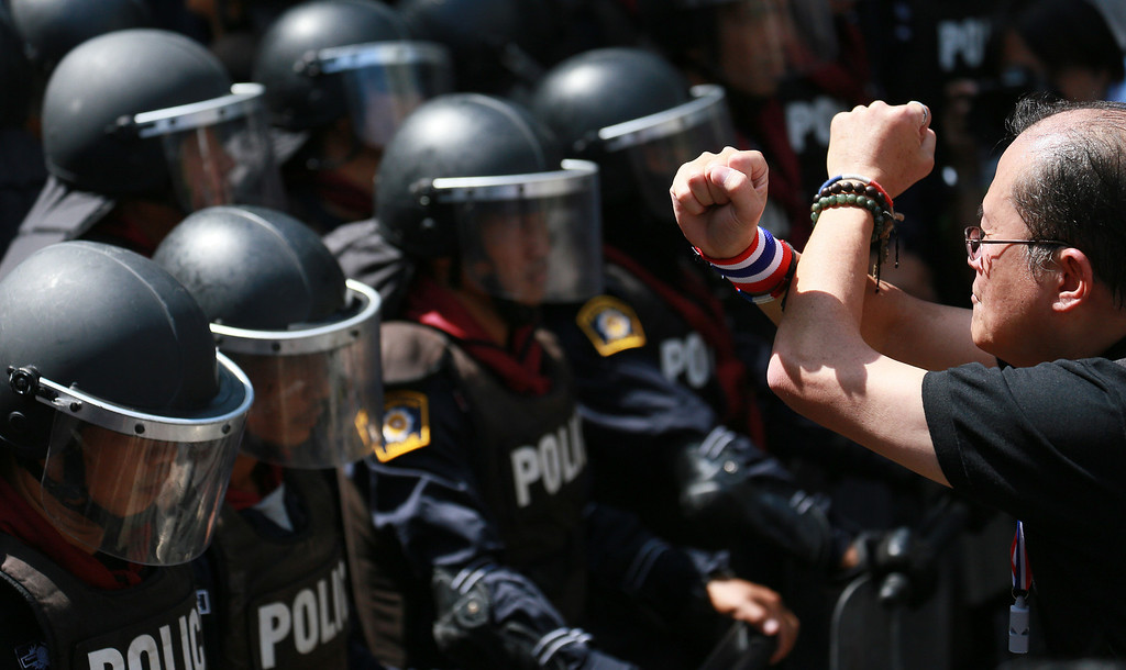 . An anti-government protester crosses his arms in front of riot police as a gesture of his opposition to the government outside the headquarters of Prime Minister Yingluck Shinawatra\'s ruling Pheu Thai Party in Bangkok, Thailand, Friday, Nov. 29, 2013. The protesters staged a rally in a bid to topple Yingluck outside the party headquarters where hundreds of riot police stood guard to prevent them from entering. (AP Photo/Wason Wanichakorn)