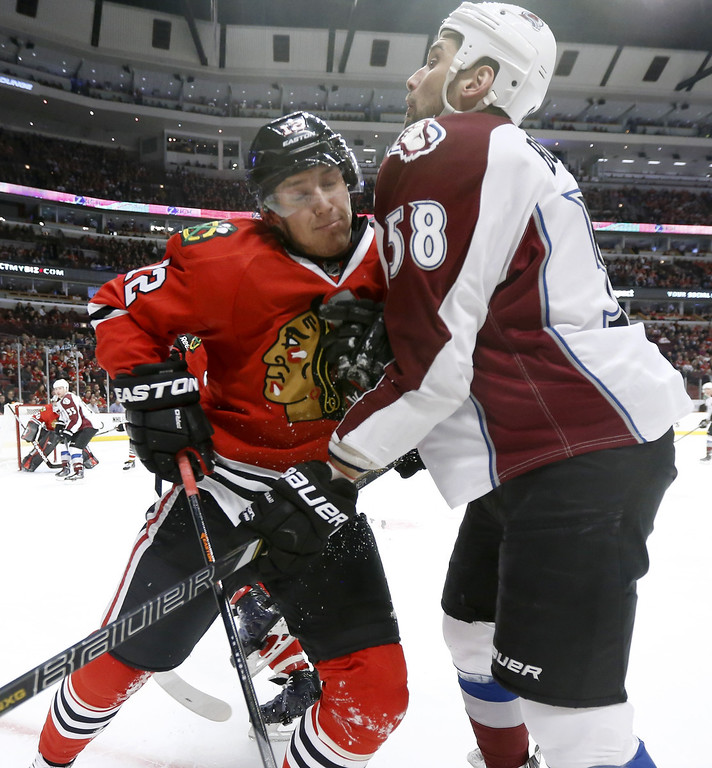 . Chicago Blackhawks center Peter Regin (12) and Colorado Avalanche left wing Patrick Bordeleau collide during the first period of an NHL hockey game Tuesday, March 4, 2014, in Chicago. (AP Photo/Charles Rex Arbogast)