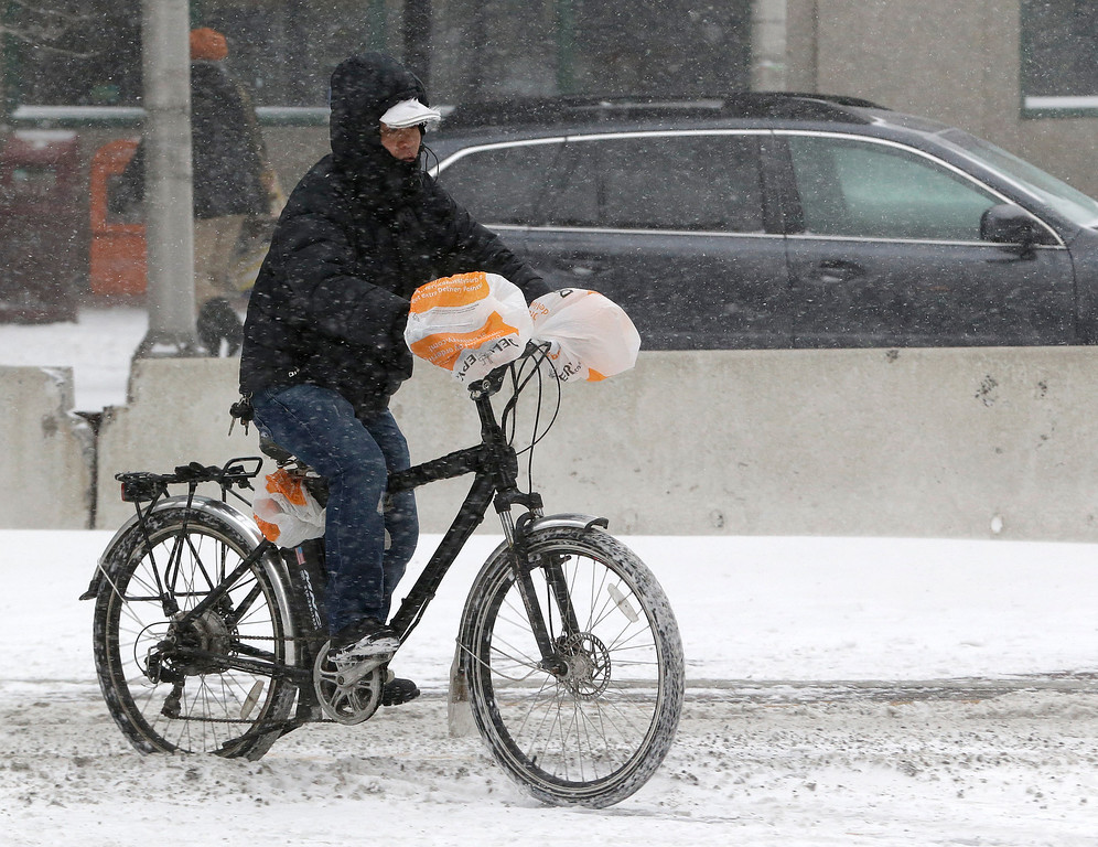 . A man uses plastic bags to cover his hands while riding a bicycle in frigid weather, Tuesday, Jan. 21, 2014, in Jersey City, N.J.  (AP Photo/Julio Cortez)