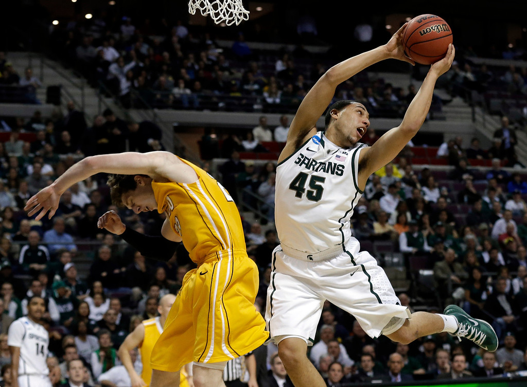 . Michigan State guard Denzel Valentine (45) grabs a rebound over Valparaiso guard Matt Kenney (23) in the first half of a second-round game of the NCAA college basketball tournament in Auburn Hills, Mich., Thursday March 21, 2013. (AP Photo/Paul Sancya)