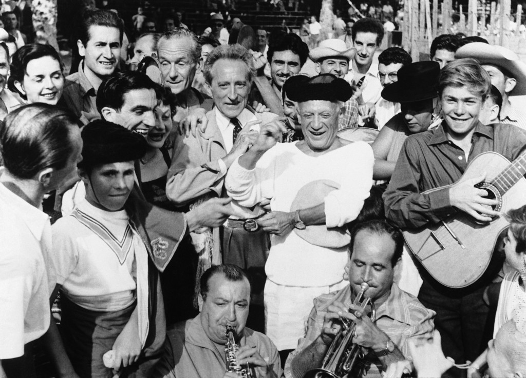 . Pablo Picasso, the 73-year-old Spanish painter, snaps his fingers to guitar music at a bullfight he organized at Vallauris, on the French Riviera, France on Aug. 7, 1955. Next to him, left, is Jean Cocteau, the French playwright. (AP Photo)