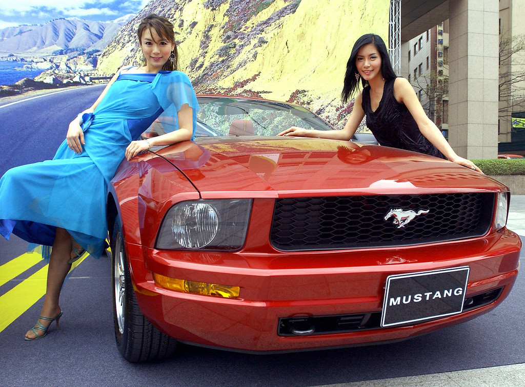 . South Korean models pose with the new Mustang of the US auto giant Ford Motors during its unveiling in downtown Seoul, 18 April 2005. The new Mustang convertible is equipped with a 4,000cc engine (six cylinders) and priced at 42.7 million won (41,752 USD).  JUNG YEON-JE/AFP/Getty Images