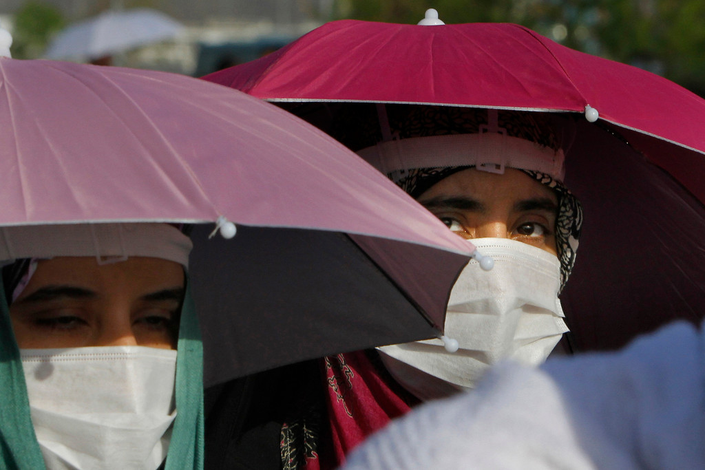 . Yemeni Muslim pilgrims wear medical masks as they walk in Arafat, near the holy city of Mecca, Saudi Arabia, Monday, Oct. 14, 2013. This year some pilgrims and security personnel are wearing masks as a precaution against the Middle East respiratory syndrome, which has stricken nearly 100 people, most of them in Saudi Arabia and the Middle East. The Saudi health minister, Abdullah al-Rabiah, said late Saturday that no cases of the coronavirus infection have been detected among pilgrims. (AP Photo/Amr Nabil)