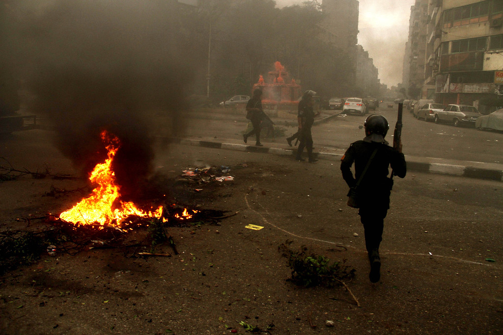 . Egyptian riot police move to disperse a protest against a new law regulating demonstrations in Cairo, Egypt, Friday, Nov. 29, 2013. (AP Photo/Ahmed Gomaa)