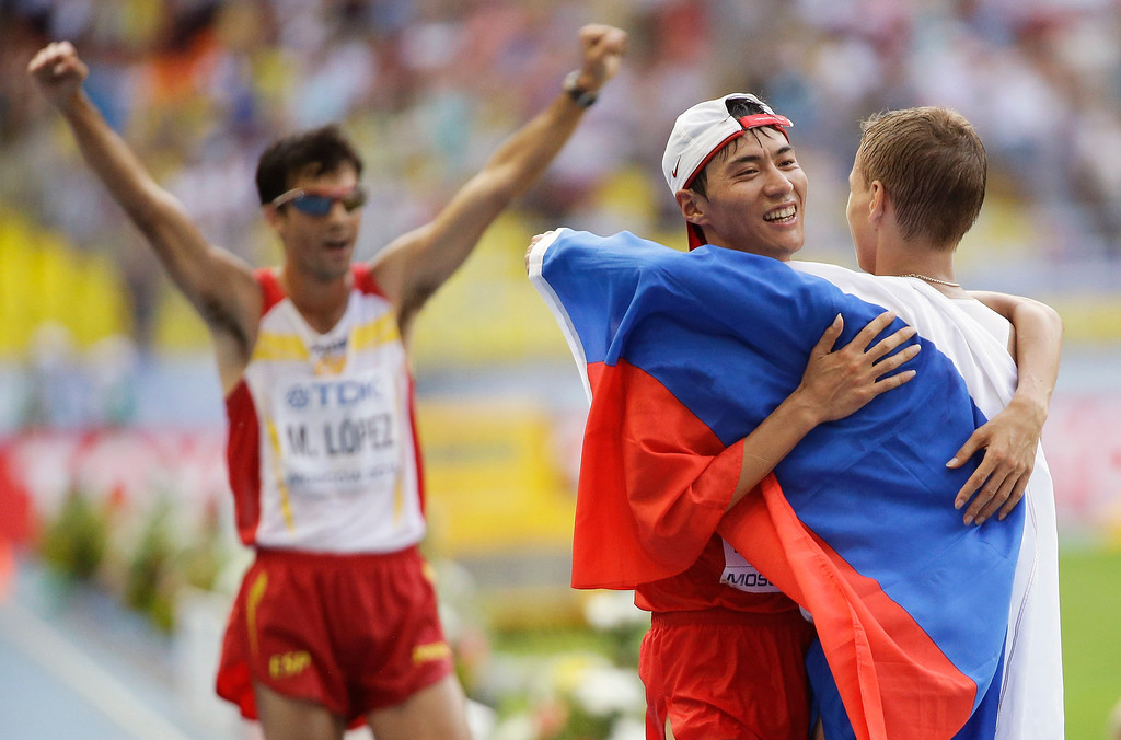 . Winner Aleksandr Ivanov of Russia, right, embraces second placed Chen Ding of China, center, as Spain\'s Miguel Angel Lopez celebrates his third place after the men\'s 20 kilometer race walk at the World Athletics Championships in the Luzhniki stadium in Moscow, Russia, Sunday, Aug. 11, 2013.  (AP Photo/Anja Niedringhaus)