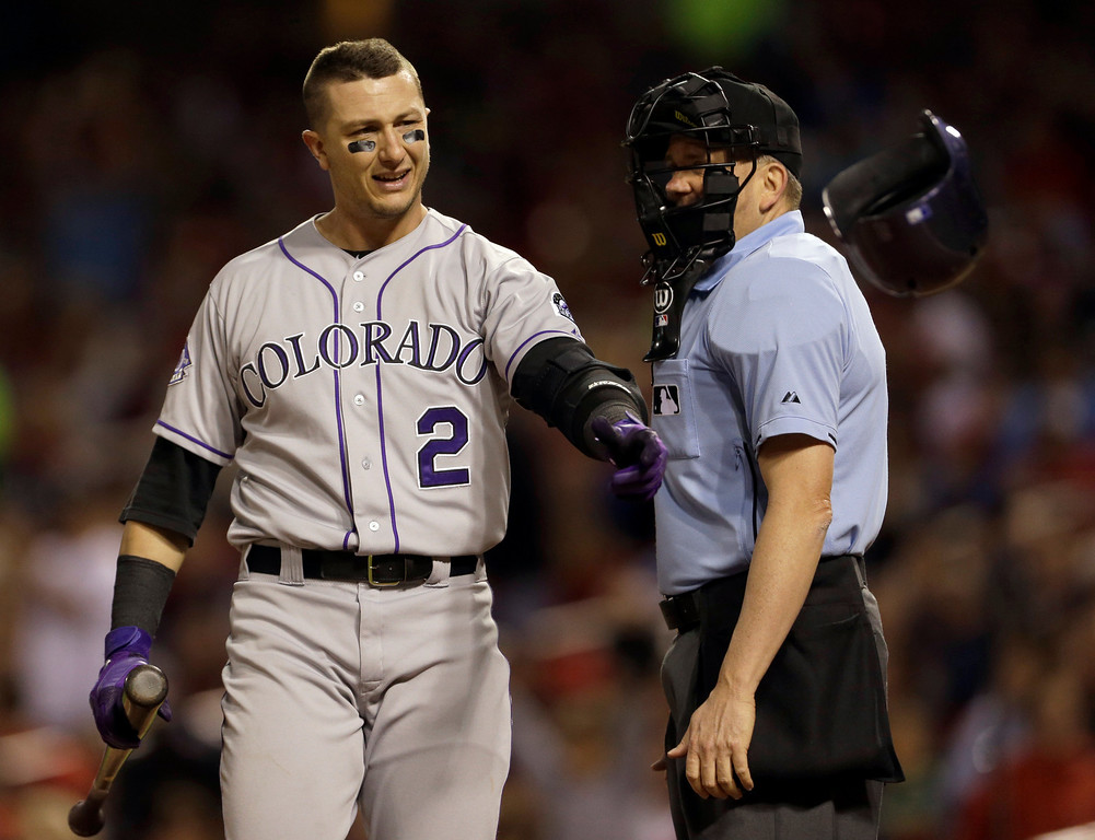 . Colorado Rockies\' Troy Tulowitzki, left, throws his helmet after being called out on strikes by home plate umpire Mike Everitt during the fourth inning of a baseball game against the St. Louis Cardinals, Friday, May 10, 2013, in St. Louis. (AP Photo/Jeff Roberson)