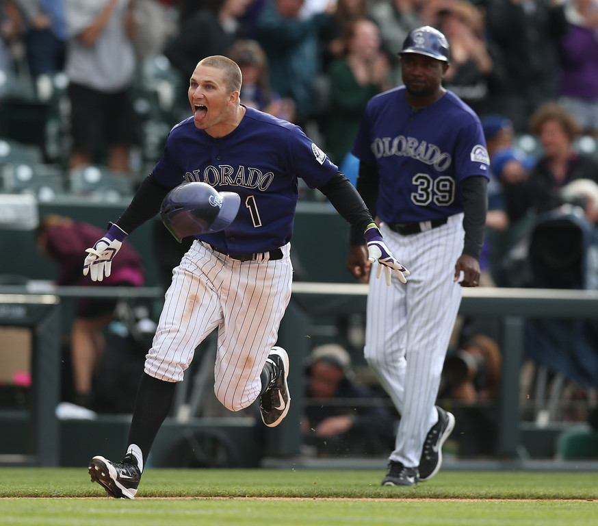 . Colorado Rockies\' Brandon Barnes, left, celebrates driving in the winning run as third base coach Stu Cole looks on against the Los Angeles Dodgers in the 10th inning of the Rockies\' 5-4 victory in 10 innings in a baseball game in Denver on Saturday, June 7, 2014. (AP Photo/David Zalubowski)