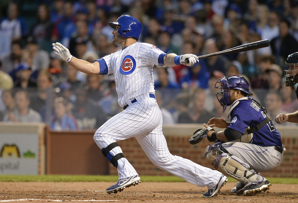 . Justin Ruggiano #20 of the Chicago Cubs hits a sacrifice fly, scoring Arismendy Alcantara during the fourth inning against the Colorado Rockies on July 28, 2014 at Wrigley Field in Chicago, Illinois.  (Photo by Brian Kersey/Getty Images)