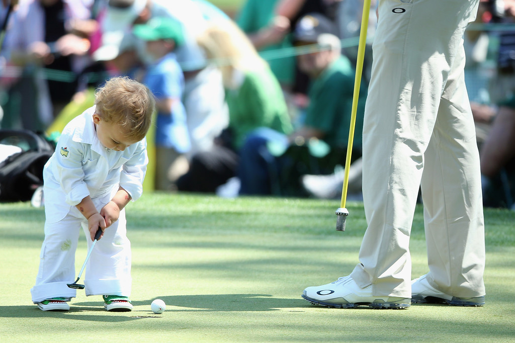 . A young caddie putts on a green during a practice round prior to the start of the 2014 Masters Tournament at Augusta National Golf Club on April 9, 2014 in Augusta, Georgia.  (Photo by Andrew Redington/Getty Images)