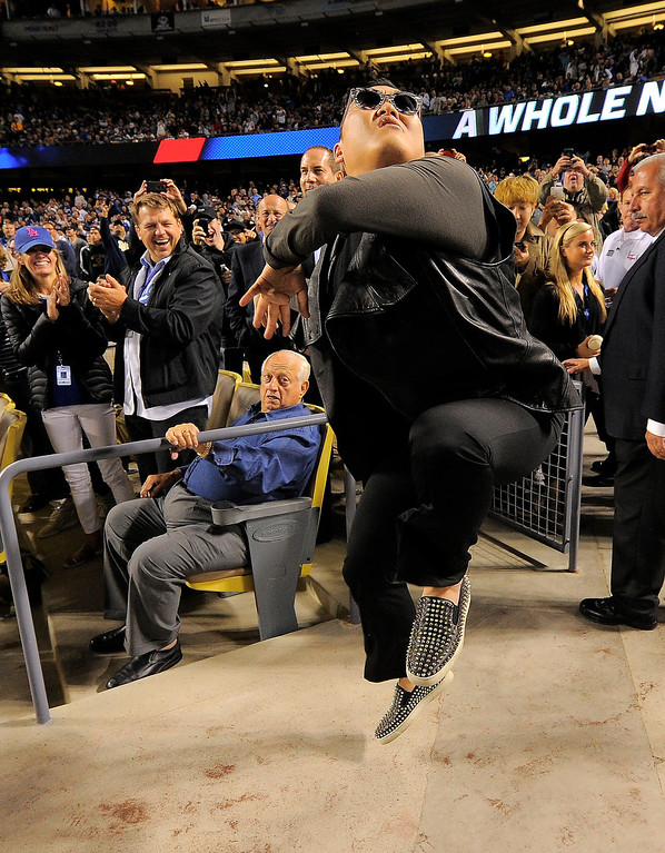 . Korean pop artist PSY dances for fans while Tommy Lasorda, sitting down, looks on as the Los Angeles Dodgers play the Colorado Rockies in their baseball game, Tuesday, April 30, 2013, in Los Angeles.   (AP Photo/Mark J. Terrill)