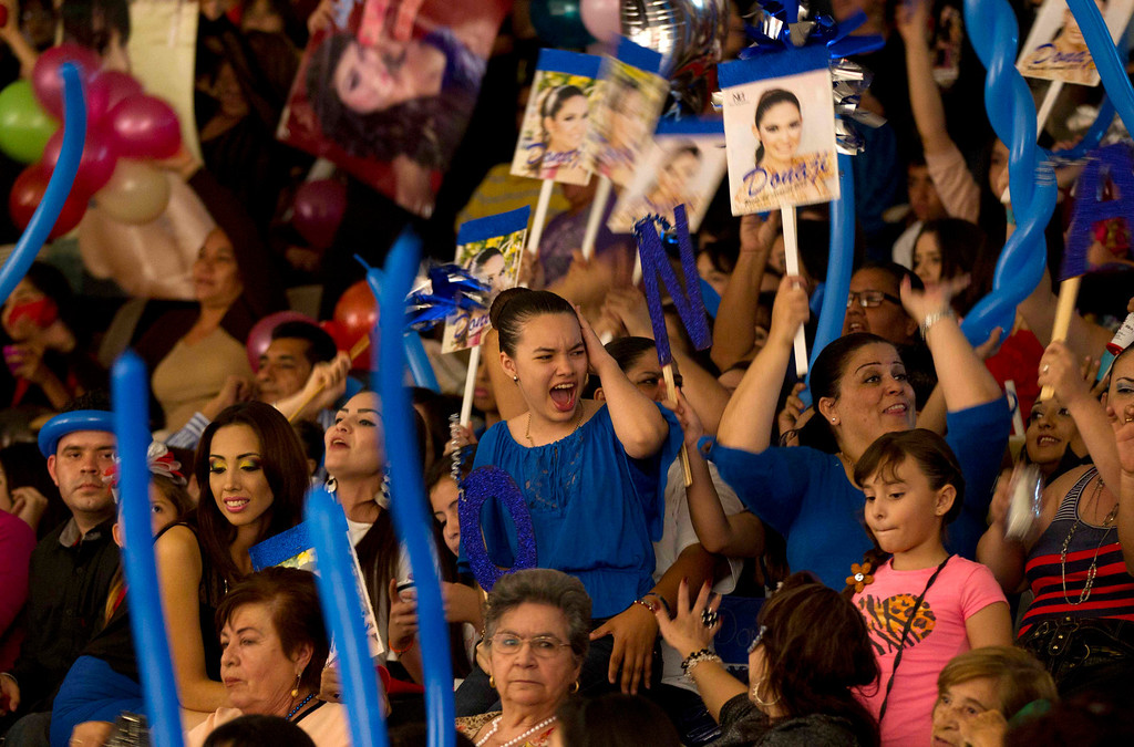 """. In this Jan. 26, 2013 photo, supporters of beauty contestant Donaji Lopez cheer for her at the \""""Guamuchil Carnival Queen 2013\"""" beauty pageant in Guamuchil, Sinaloa state, Mexico. Residents packed the local theater filled with banners and posters advertising the queens and filled the aisles and stairways with extra chairs after the seats filled. (AP Photo/Eduardo Verdugo)"""