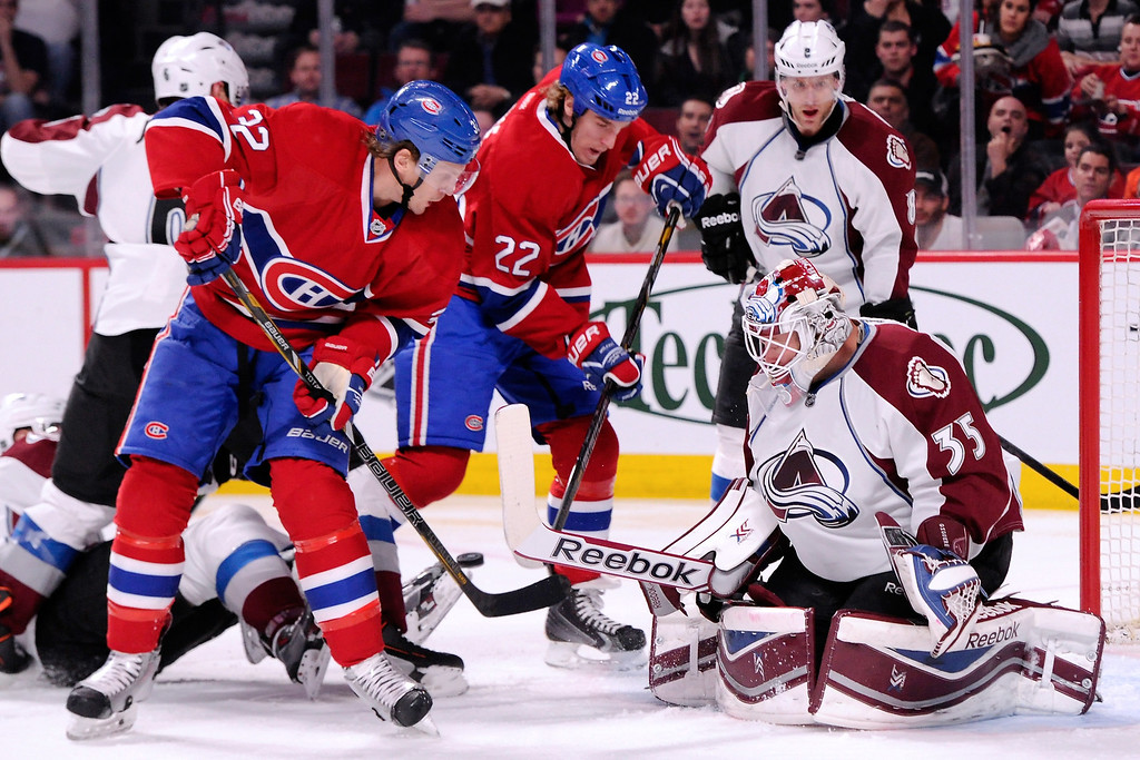. MONTREAL, QC - MARCH 18:  Travis Moen #32 of the Montreal Canadiens deflects the puck against Jean-Sebastien Giguere #35 of the Colorado Avalanche during the NHL game at the Bell Centre on March 18, 2014 in Montreal, Quebec, Canada.  (Photo by Richard Wolowicz/Getty Images)